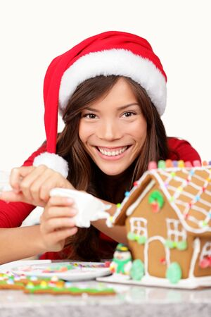Christmas girl making Gingerbread house  Young woman in santa hat doing Christmas preparations putting icing on gingerbread house  Mixed race Asian   Caucasian model wearing santa hat  photo