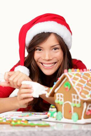 decoracion de pasteles: Navidad niña haciendo Gingerbread mujer joven casa en santa sombrero haciendo preparativos de Navidad que ponen la guinda gingerbread house mezclado modelo raza caucásica asiática llevaba sombrero de santa