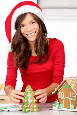 Christmas activities - girl making gingerbread house  Young woman in Christmas preparations putting icing on gingerbread house  Model wearing santa hat Stock Photo - 15089334