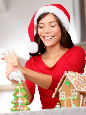 Gingerbread house  Young santa hat woman in Christmas preparations putting icing on gingerbread house  Mixed race Asian   Caucasian woman model wearing santa hat  photo