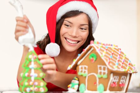 Girl making Christmas gingerbread house Jeune femme dans les pr�paratifs de No�l mettant cerise sur mod�le gingerbread house chapeau de Santa photo