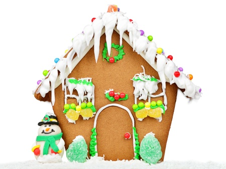 Gingerbread house isolated on white background in studio with Christmas tree and snowman