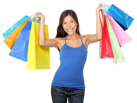 Shopping woman holding shopping bags above her head smiling happy during sale shopping spree