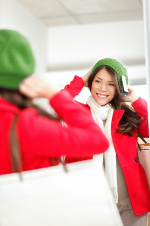 Fall   Winter shopping woman trying on knit hat looking in mirror  photo