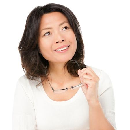 mujeres pensando: Pensando en la mujer madura asi�tica sosteniendo gafas gafas mirando hacia el lado en espacio de la copia Mujer china asi�tica madura aislada en el fondo blanco en estudio Foto de archivo