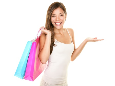 Shopping woman showing something mit offener Handfläche lächelt fröhlich