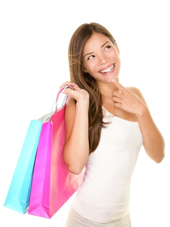 Shopping woman thinking looking up at copy smiling fresh and happy  Foto de archivo