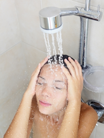 Woman in shower enjoying water splashing on face and hair washing  Pretty serene multicultural Caucasian   Asian Chinese female model in bathroom  photo