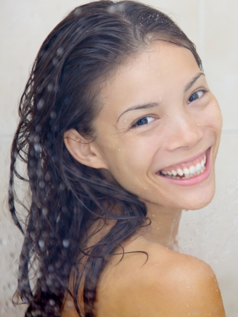 hair shampoo: Closeup portrait of woman in shower smiling happy looking at camera  Mixed-race Asian Chinese   Caucasian female model in shower  Stock Photo