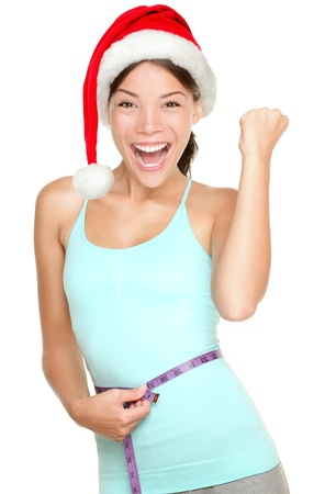 Christmas fitness woman excited about weight loss measuring waist with measuring tape wearing santa hat screaming excited  Mixed race fitness model isolated on white