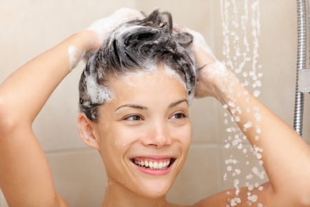 Mujer lavar el cabello con champú en espuma de ducha sonriendo feliz mirando correr el agua caliente hermosa raza mixta chino asiático modelo femenino caucásico en el baño Foto de archivo