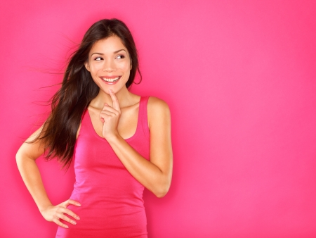 Thinking beautiful young woman looking to the side at pink copyspace. Funky fresh and playful multiracial Asian Chinese  Caucasian smiling happy and joyful on pink background. photo