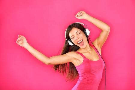 Woman dancing hört Musik in den Kopfhörern vom Smartphone oder MP3-Player. Sexy glückliche junge Frau tanzt auf rosa Hintergrund aufgeregt. Weibliche Modell der gemischten Ethnizität, Asiatisch Chinesisch und kaukasischen.