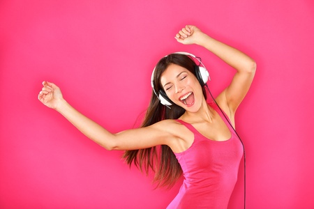 Woman dancing listening to music in headphones from smart phone or mp3 player. Sexy happy young woman dancing excited on pink background. Female model of mixed ethnicity, Asian Chinese and Caucasian.
