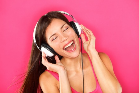earbud: Music. Woman listening to music on headphones enjoying a dance. Closeup portrait of asian girl on pink background
