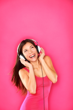 Woman listening to music wearing headphones dancing happy smiling and joyful on pink background. Funky fresh multiracial Caucasian  Asian Chinese female model