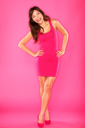 Sexy laughing confident woman in pink dress smiling flirtatious standing on pink background in full length. Beautiful mixed race asian chinese / caucasian female fashion model.