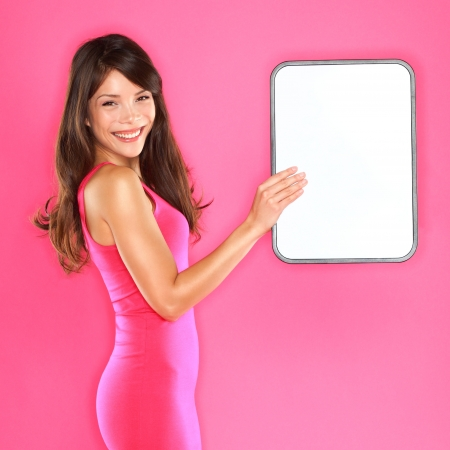 board: Woman holding showing sign. Sexy beautiful young playful woman holding white blank sign board with copyspace. Mixed-race Asian Chinese  Caucasian female model on pink background.