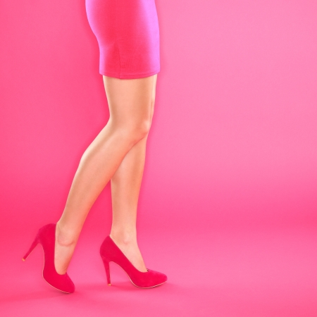 Legs and pink high heels shoes. Closeup of woman legs and shoes on pink background. photo