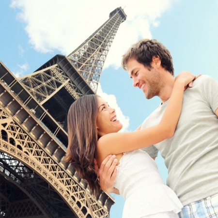 Paris Eiffel tower romantic couple embracing kissing in front of Eiffel Tower, Paris, France. Happy young interracial couple, Asian woman, Caucasian man. photo
