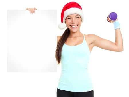 Kerst fitness vrouw showing teken staan met rode santa hoed geïsoleerd op witte achtergrond. Fit glimlachend gelukkig geschiktheid model van gemengde Aziatische Chinese en Kaukasische etniciteit. Stockfoto