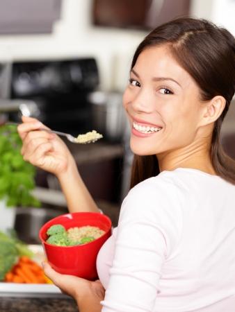 Vrouw eet quinoa broccoli salade Eet gezond voedsel lifestyle concept met mooie jonge multiraciale vrouw in haar keuken