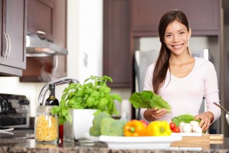 그녀의 20 대 젊은 다문화 백인 아시아 중국 여자는 야채와 함께 건강 식품을 만드는 새로운 부엌에서 요리하는 여자