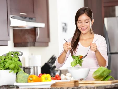 Vrouw die salade in de keuken Gezond eten lifestyle concept met mooie jonge vrouw koken in haar keuken Stockfoto
