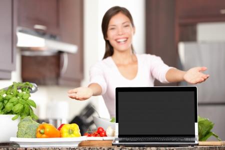 Vrouw die laptop toont koken in de keuken Focus op het scherm met een kopie ruimte Opgewonden gemengd ras Aziatische Kaukasische jonge vrouw in haar keuken Stockfoto