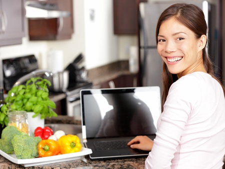 Woman using laptop computer in kitchen with greens and vegetables  Lifestyle cooking concept with smiling happy mixed-race Asian chinese Caucasian woman working sitting in her kitchen  Stock Photo