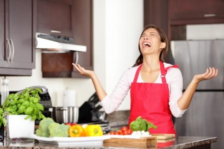 Lustig Kochen Bild der Frau weinend und schreiend in der Küche aufzugeben Zubereitung von Essen nach erfolgloser Kochen Versuch Schöne junge Mixed-Rennen asiatischen chinesischen kaukasischen Frau in der Küche