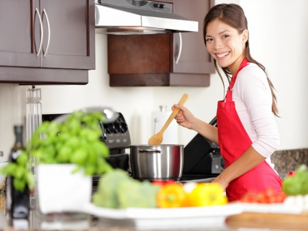Cooking woman in kitchen stirring in pot making food for dinner  Young housewife smiling happy looking at camera  Mixed-race Caucasian   Asian chinese woman in her twenties  Archivio Fotografico