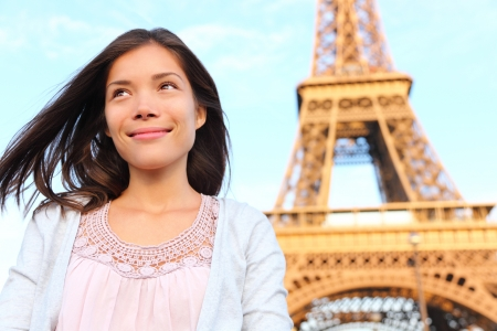 Eiffel tower Paris tourist woman smiling happy  Beautiful portrait of multiracial Asian Caucasian girl during travel in Europe  photo