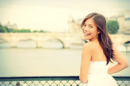 french woman: Paris woman laughing joyful and candid in Paris on brige on river Seine  Fresh energetic young mixed race Asian Caucasian female model joyful  Stock Photo