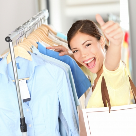 Shopping - Happy shopper woman showing thumbs up excited holding shopping bag in clothing store looking for clothes on sale  Beautiful mixed race asian caucasian woman model