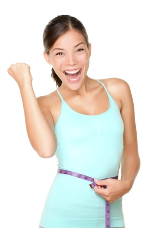 Weight loss concept woman smiling happy excited holding measuring tape around waist  Energetic portrait of sport fitness model isolated on white background  Mixed race Caucasian   Asian woman  Archivio Fotografico