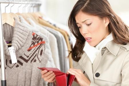 Leere Geldbörse oder Brieftasche - kein Geld für Shopping-Konzept Woman shopping für Kleidung in Bekleidungsgeschäft