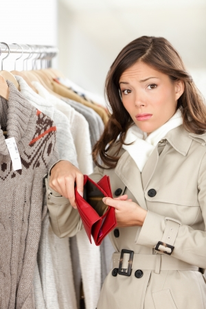 Woman shopper holding empty wallet or purse while shopping in store  Sad young woman looking at camera in clothing shop
