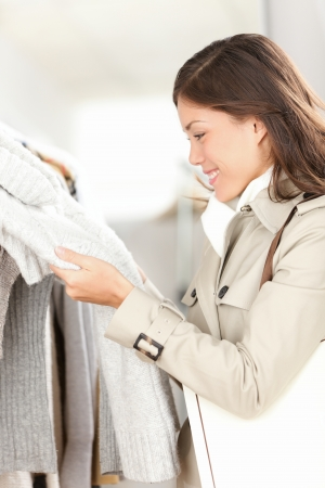 Clothes shop - woman shopping looking at clothes in store shop  Beautiful mixed race asian casuasian girl lifestyle image