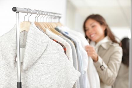 洋服: 衣料品女性服衣料品ラック フォーカスのフォア グラウンドでの冬のセーターを見て店でのショッピング 写真素材