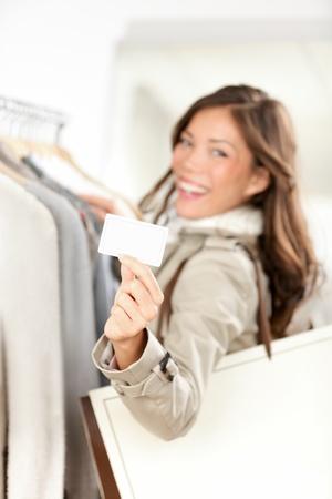 Shopping Geschenkkarte Frau glücklich zeigt Visitenkarte oder leere Papier Schild in Bekleidungsgeschäft Schöne lächelnde gemischten Rennen asiatischen kaukasischen jungen Modell
