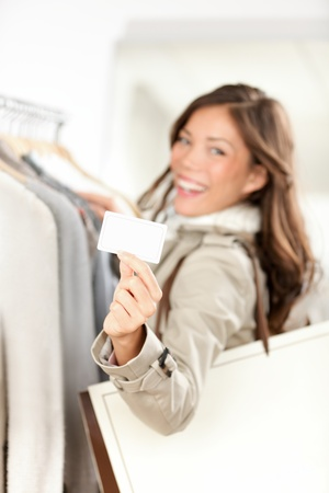 Shopping gift card woman happy showing business card or blank paper sign in clothes shop  Beautiful smiling mixed race Asian Caucasian young model