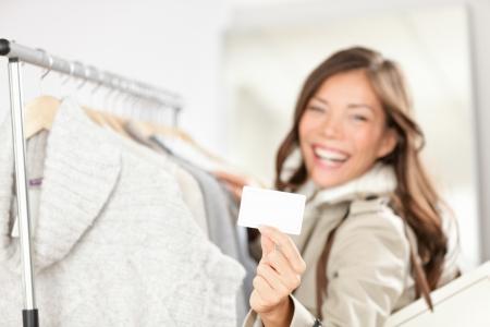 Geschenkkarte Frau beim Einkaufen Kleidung Happy shopper holding Ergebnis Geschenk oder Visitenkarte im Speicher während des Einkaufs für Kleidung