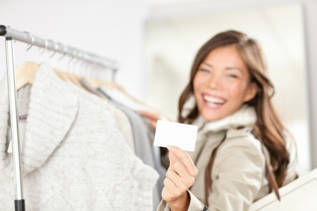Gift card woman shopping clothes  Happy shopper holding showing gift card or business card in store while shopping for clothing  photo