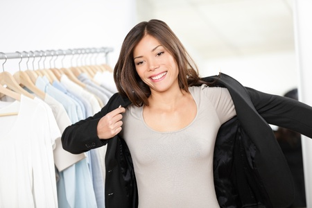 fitting: Woman shopping for business suit clothes in clothing store trying on jacket for businesswoman  Beautiful young professional business woman of mixed Asian Chinese   Caucasian ethnicity looking in mirror  Stock Photo