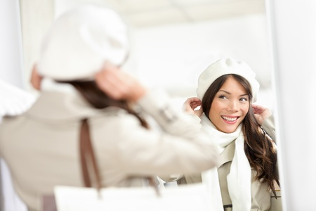 Winter shopping woman  Shopper trying on hat in clothes store during sale  Multiracial woman looking in mirror