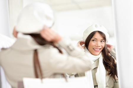 Winter winkelen vrouw Shopper probeert op hoed in kleding winkel tijdens verkoop Multiraciale vrouw op zoek in spiegel Stockfoto