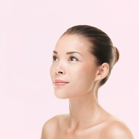 Multiracial ethnic Asian and Caucasian female beauty model looking to the side and up on bright pink background. photo