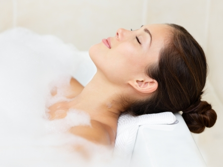 lying in bathtub: Bath woman relaxing bathing in bathtub with bath foam Stock Photo