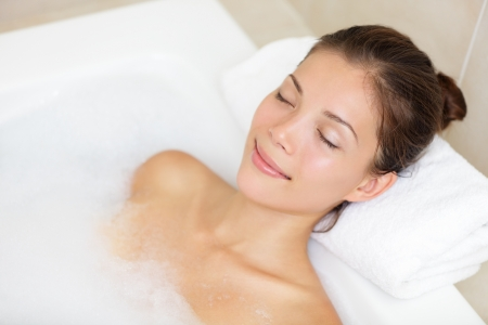 resting: Bathing woman relaxing in bath smiling relaxing with eyes closed Stock Photo